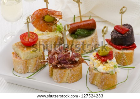 Spanish cuisine. Montaditos. Sliced bread topped with a variety of appetizers. Spanish Tapas. Two glasses of Sherry wine in the background.