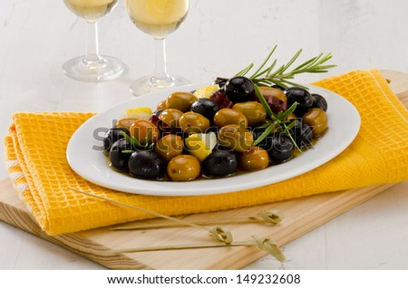 Spanish cuisine. Tapas. Marinated Olives in a white plate.Two glasses of Sherry Wine in the background. Selective Focus.