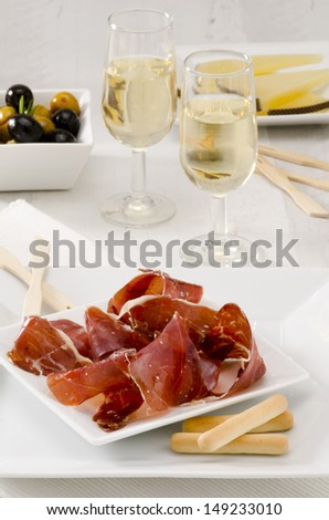 Spanish cuisine. Tapas. Sliced Serrano Ham in a white plate.Two glasses of Sherry Wine in the background. Selective Focus. Jamon Serrano. - stock photo