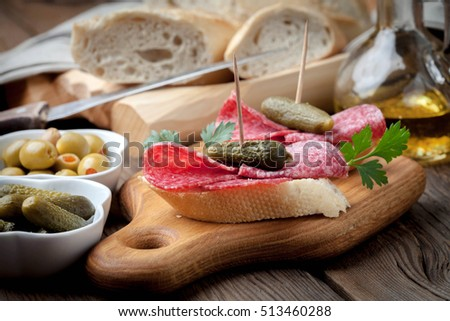 Spanish cuisine. Tapas with sliced salami, olives and cucumber on a wooden table. on a wooden table.