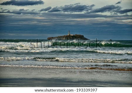 Spanish destination on Atlantic Ocean, Somo beach in Cantabria region, view on lighthouse