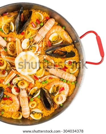 Spanish dish paella with seafood in traditional pan, view from above.  Isolated on a white background. - stock photo