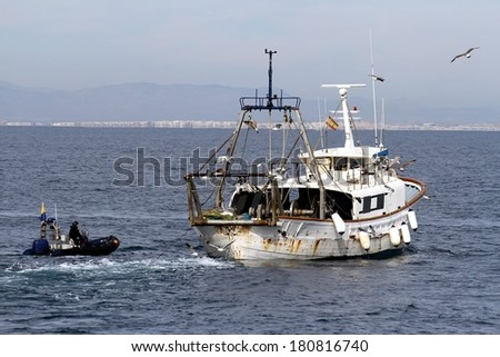 Spanish fish inspectors working in a trawler boat - stock photo
