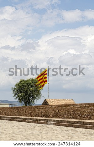 spanish flag, ancient street and cloudscape - stock photo