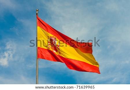 spanish flag on a pole over beautiful sky - stock photo