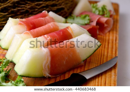 Spanish jamon with melon on wooden table.Melon with serrano ham, a typical dish in Spain.Selective focus.