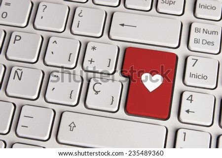 Spanish keyboard with love concept heart shape icon over red background button. Image with clipping path for easy change the key color and editing. - stock photo