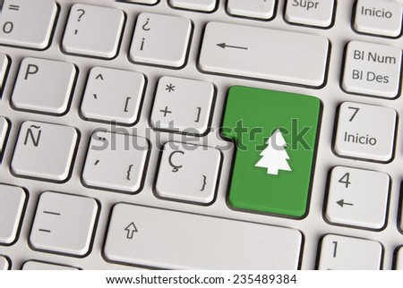 Spanish keyboard with Merry Christmas tree icon over green background button. Image with clipping path for easy change the key color and editing. - stock photo