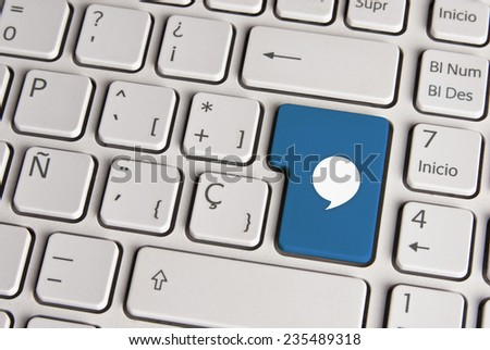 Spanish keyboard with social media message bubble icon over blue background button. Image with clipping path for easy change the key color and editing.