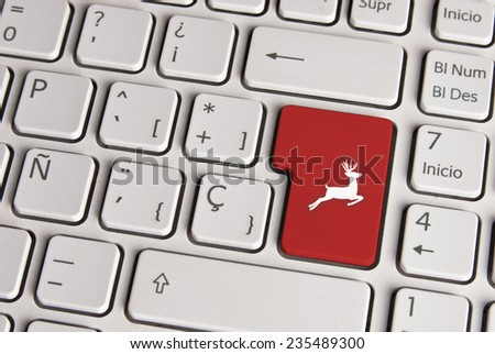 Spanish keyboard with vintage christmas reindeer icon over red background button. Image with clipping path for easy change the key color and editing. - stock photo