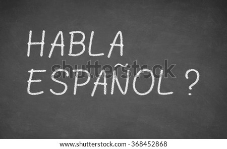 Spanish language learning concept image. Teacher or student wrote HABLA ESPANOL on blackboard during spanish language course class.