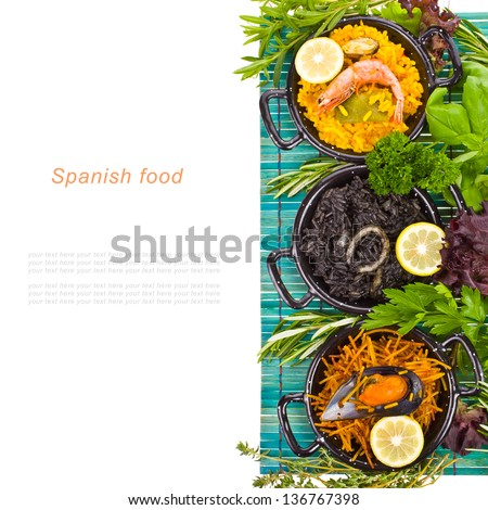 Spanish Mediterranean sea food - black rice, paella, noodles in a typical small pan on the blue mat isolated on white background - stock photo