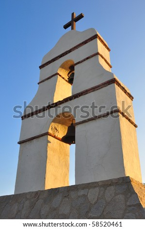 Spanish mission bell tower against blue sky. - stock photo