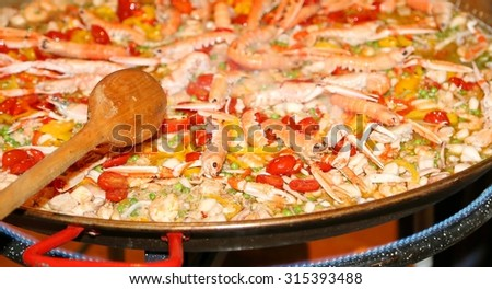 Spanish paella with prawns and rice cooked on a pot in the restaurant