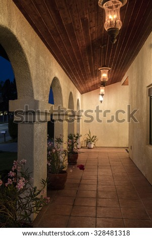 Spanish porch of this Mediterranean house presented in a stucco finish with wooden ceiling and fitting hanging lights.  - stock photo