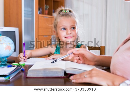 spanish private teacher and little girl studying with notes at home