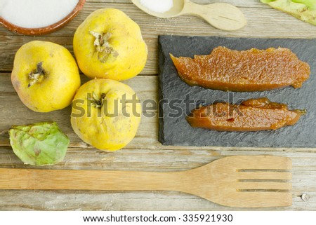 Spanish quince fruits and paste with ingredients on wooden background - stock photo