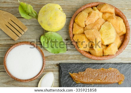 Spanish quince paste on a slate plate and ingredients on wooden background - stock photo