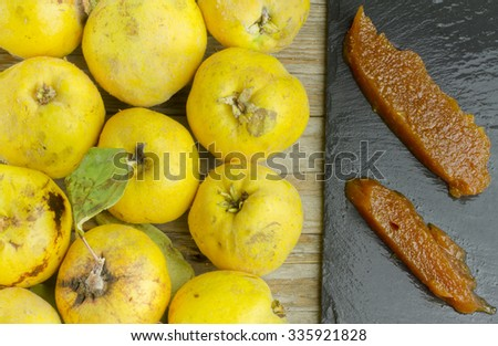 Spanish quince paste slices on a slate plate with quince fruits on wooden background - stock photo