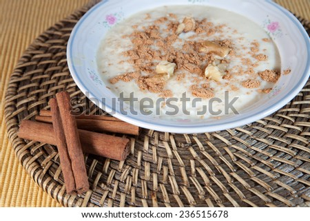 Spanish rice with milk, delicious homemade recipe decorated with cinnamon branches over natural fiber place mat