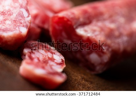 Spanish salami on wooden background close up with shallow DOF. - stock photo