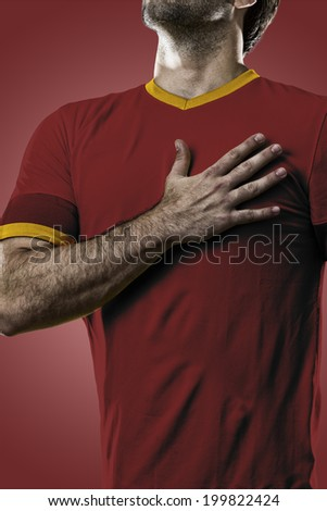 Spanish soccer player, listening to the national anthem with his hand on his chest. On a red background.