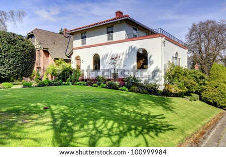 Spanish style white large home front exterior with large green lawn. - stock photo