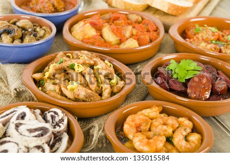 Spanish Tapas & Crusty Bread - chorizo al vino, gambas pil pil, patatas bravas, albondigas a la jardinera, setas al ajillo, pollo al limon con ajo, rollitos de pollo con aceitunas, tomates al ajillo - stock photo