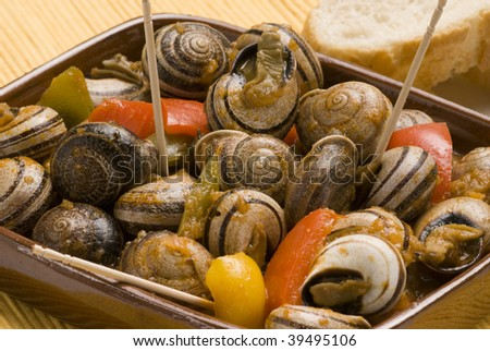 Spanish tapas. Snails in chili sauce. Closeup. Typical appetizer. - stock photo