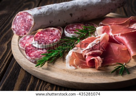 Spanish tapas with jamon, glass and bottle of beer on a wooden background - stock photo