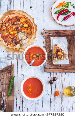 Spanish traditional tomato soup Gazpacho with ricotta tart from above on a rustic kitchen styling table.  - stock photo