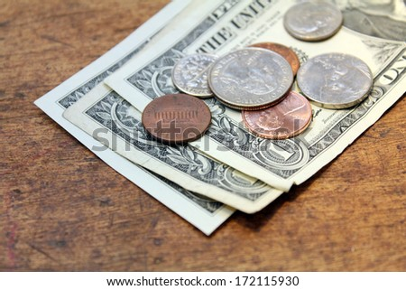 spare change dollars and cents over wood background