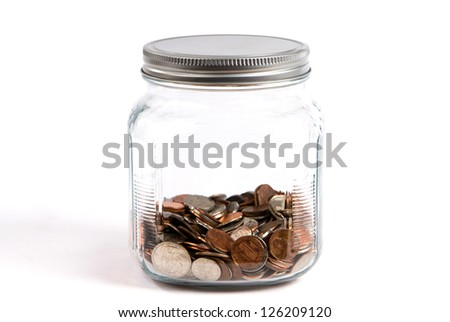 Spare change jar or piggybank holds coins in a glass container on white background. - stock photo