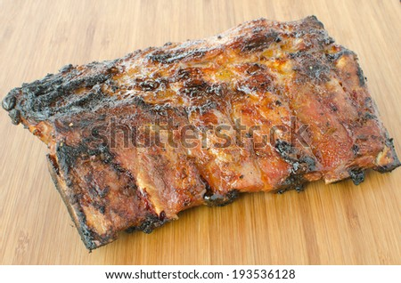 Spareribs on grill with dip, toasted baguette