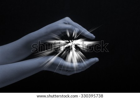 Spark of hope in a woman hand on dark background. The light of faith. Light protection . - stock photo