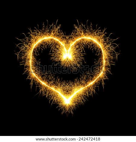 Sparking heart over black background - stock photo
