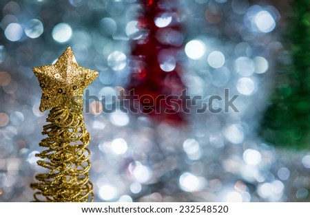 Sparkle coated wire Christmas tree decorations in gold, red and green. Out of focus lights in on silver background. - stock photo
