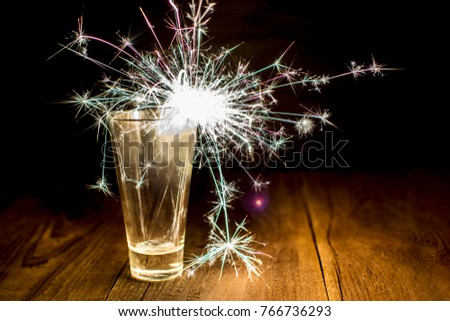 sparkler. Bengal fire burns in a glass on a dark background. A glass with a Bengal burning fire stands on a wooden surface