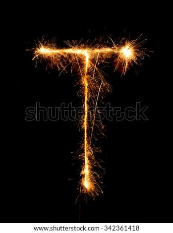 Sparkler firework light alphabet T (Capital Letters) at night background - stock photo