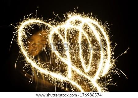 Sparkler heart on black background - stock photo