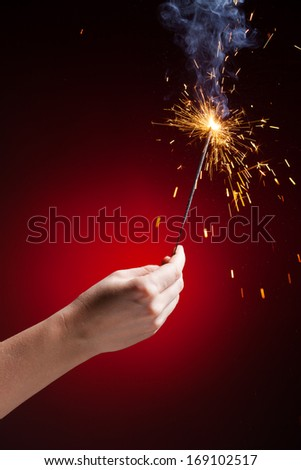 sparkler in hand, close-up view, red background