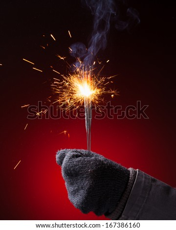 sparkler in hand mitten, close-up view, red background - stock photo