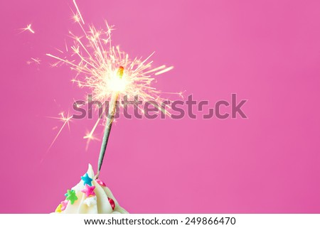 Sparkler on a cupcake with copyspace to side - stock photo