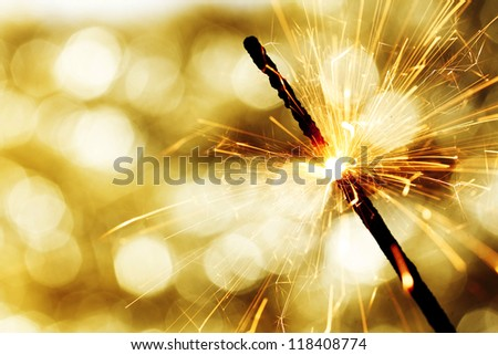 sparkler on gold  bokeh background macro close up - stock photo