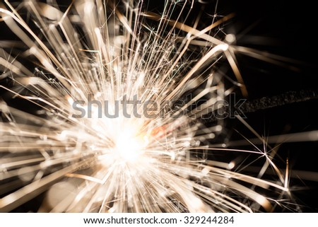 sparkler or Bengal fire on a dark background - stock photo