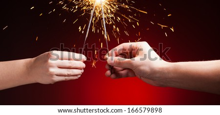 sparklers in hands, close-up view, red background - stock photo