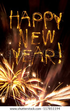 Sparklers spell Happy New Year above gold fireworks burst - stock photo