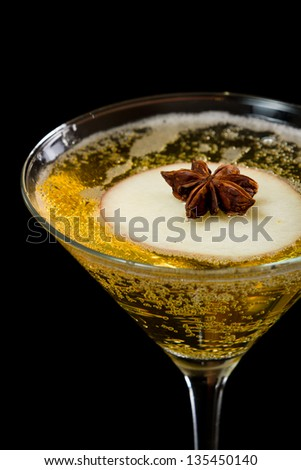 sparkling apple martini isolated on a dark bar with an anise star floating on an apple slice - stock photo