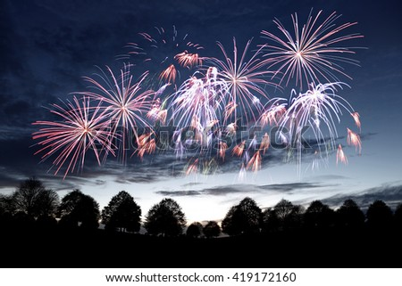 Sparkling celebrative firework explosion over a surreal evening sky.