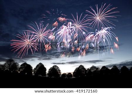 Sparkling celebrative firework explosion over a surreal evening sky.  - stock photo